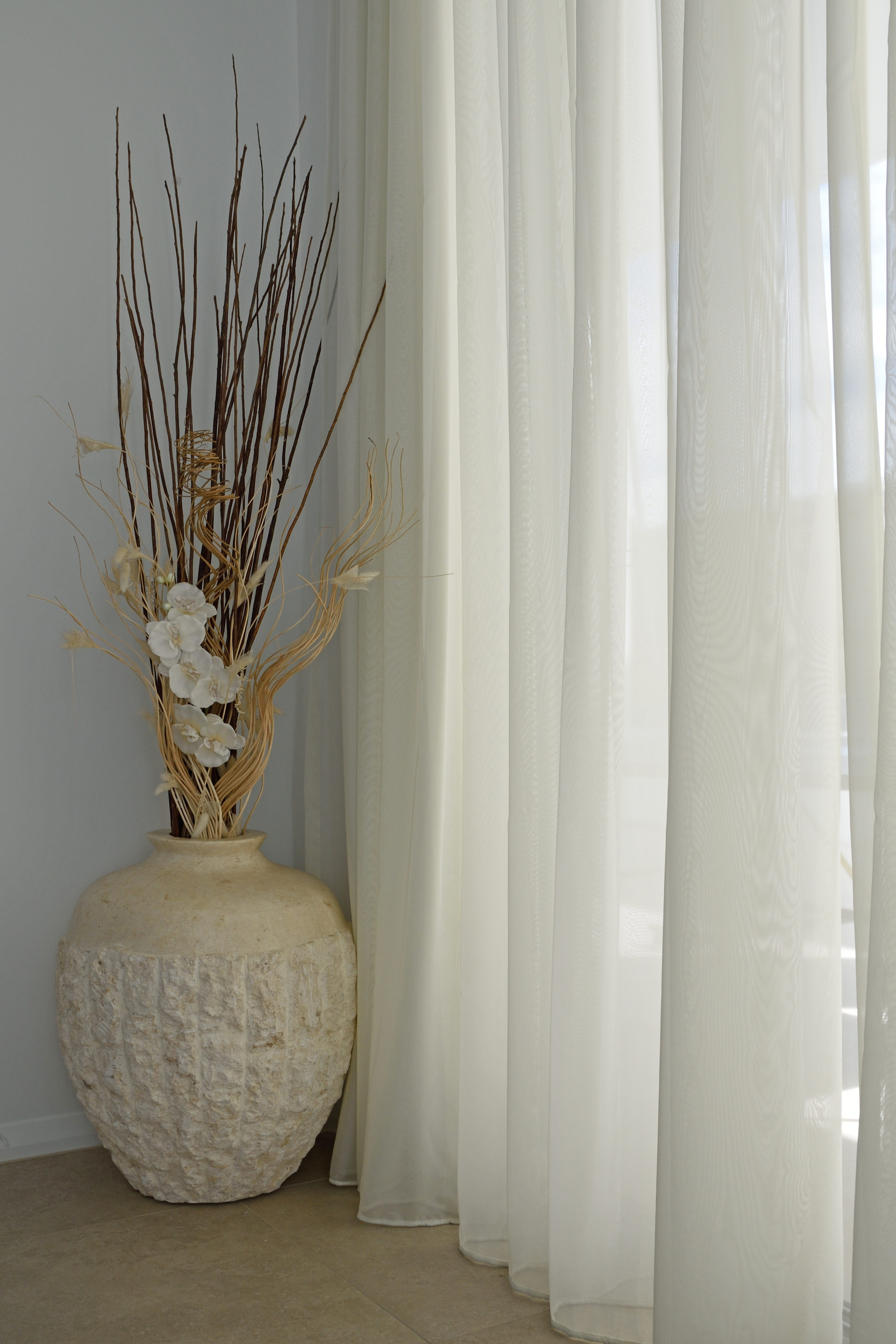 Inverted pleat sheer from ceiling with vase