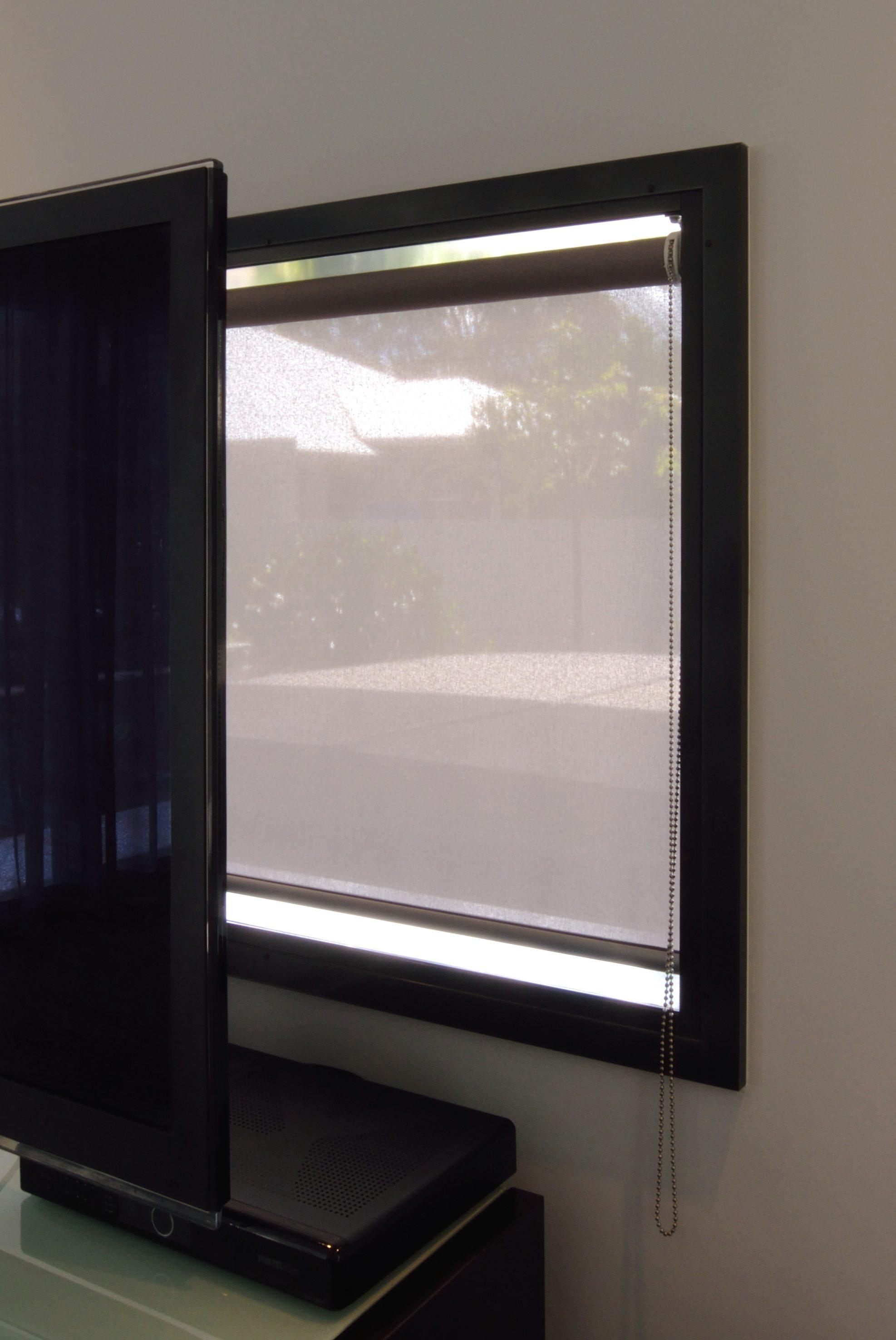 Sun control roller blind behind TV